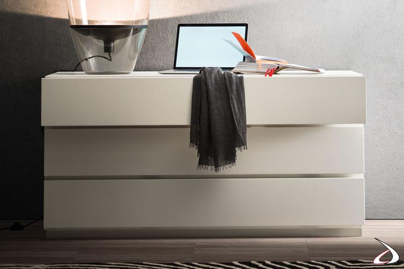 Comò a tre cassetti in laccato bianco opaco, con apertura nascosta per mantenere un design pulito e minimalista.