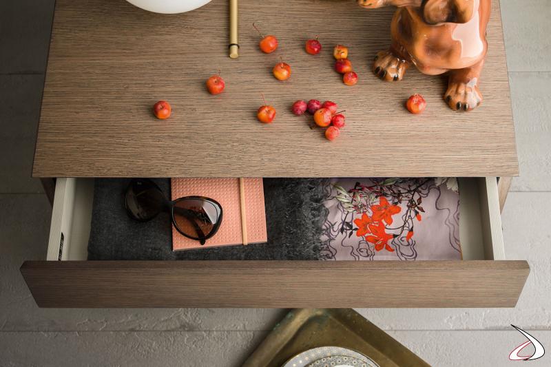 Comodino dal design minimalista, caratterizzato da una finitura in rovere in contrasto con il rivestimento interno dei cassetti.