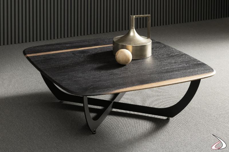 Tavolino dal top sagomato in rovere cotto. Il suo design semplice è in contrasto con il particolare basamento incrociato.