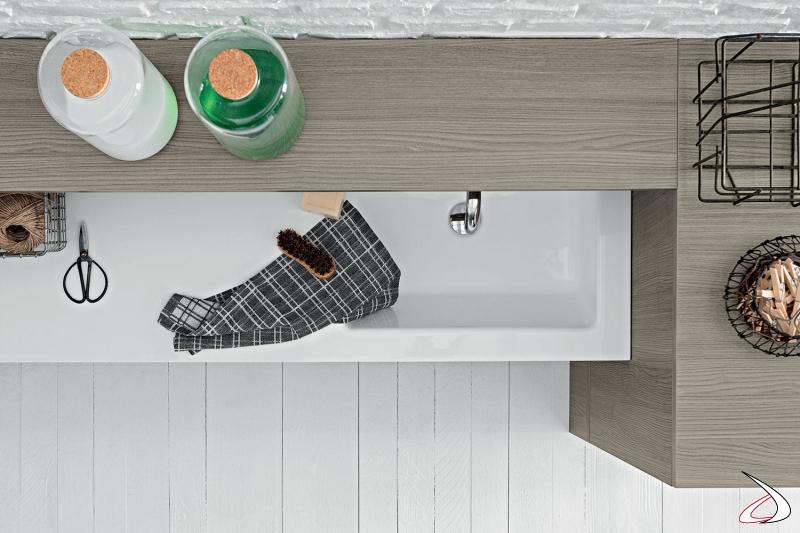 Lavanderia moderna con ampio lavatoio in marmo minerale e mensola porta saponi