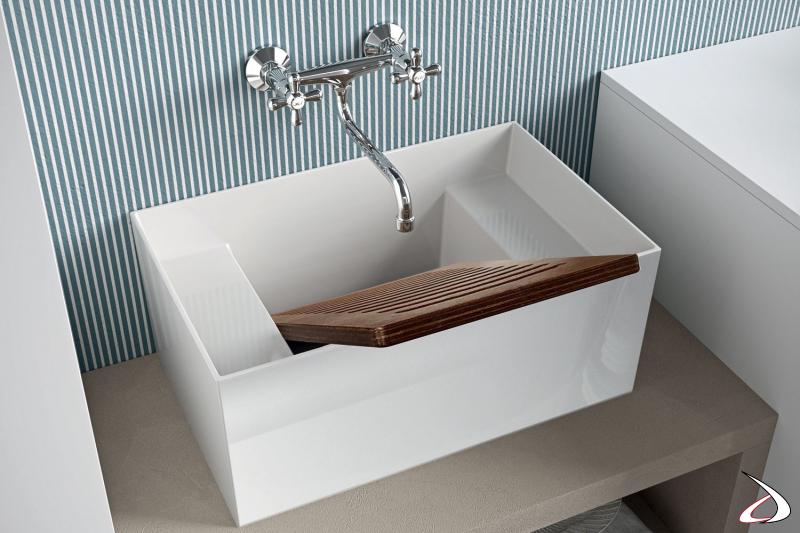Lavanderia con ampio lavatoio in ceramica e asse in legno