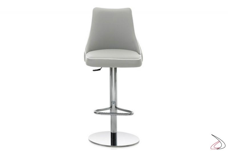Sgabello con basamento centrale in acciaio cromato e seduta in eco-pelle grigio chiaro e bordino in contrasto bianco.