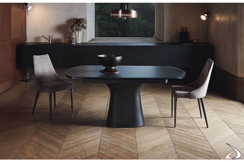Tavolo allungabile a botte di design con piano in cristallo antigraffio e basamento in cemento