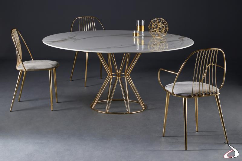 Tavolo rotondo Circus con struttura in acciaio cromato ottone e piano in marmo bianco statuario. Sedia Waiya.
