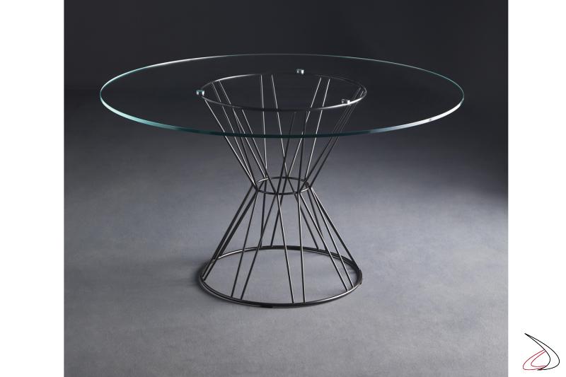 Tavolo Circus con struttura in acciaio verniciato grigio piombo e piano rotondo in cristallo trasparente.
