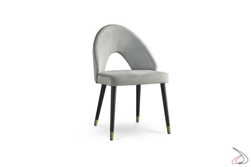 Sedia con schienale forato struttura in legno e seduta in tessuto.