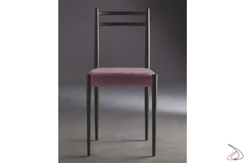 Sedia con struttura in legno color nero e seduta in tessuto rosa pastello.
