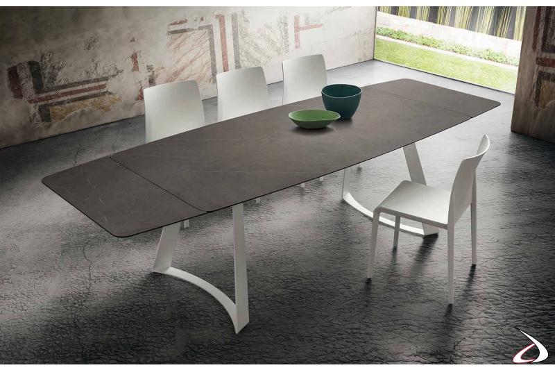 Tavolo design allungabile con gambe ad arco e piano a botte in hpl stratificato