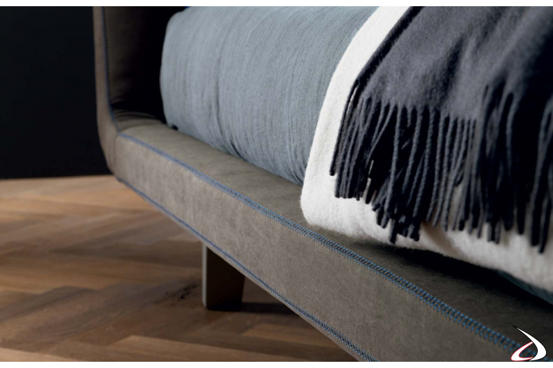 Upholstered bed in fabric with stitching