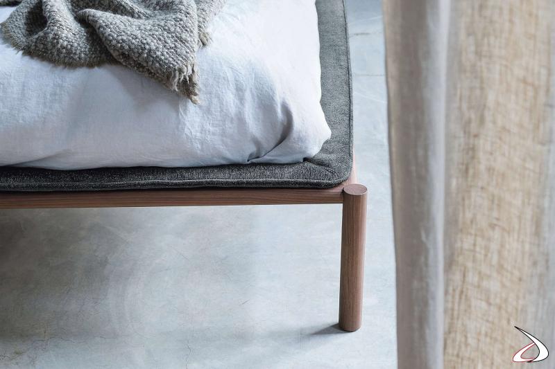 Letto moderno con piedini alti in legno noce canaletto e coprigiroletto imbottito