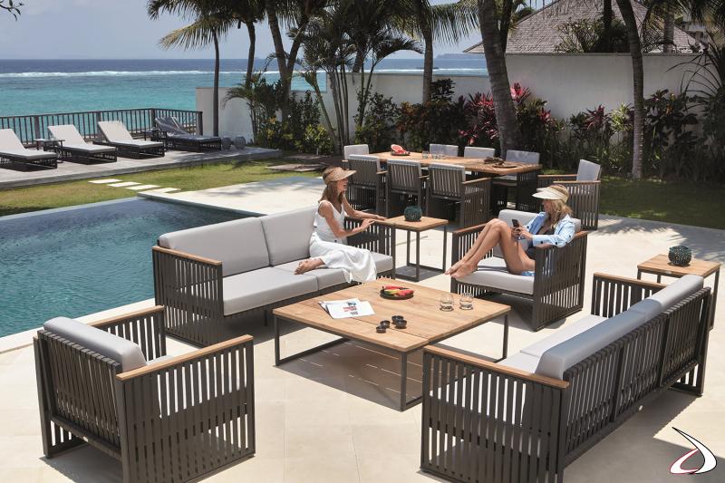 Salotto da bordo piscina di design con poltrone e divani con cuscini e braccioli alti in teak