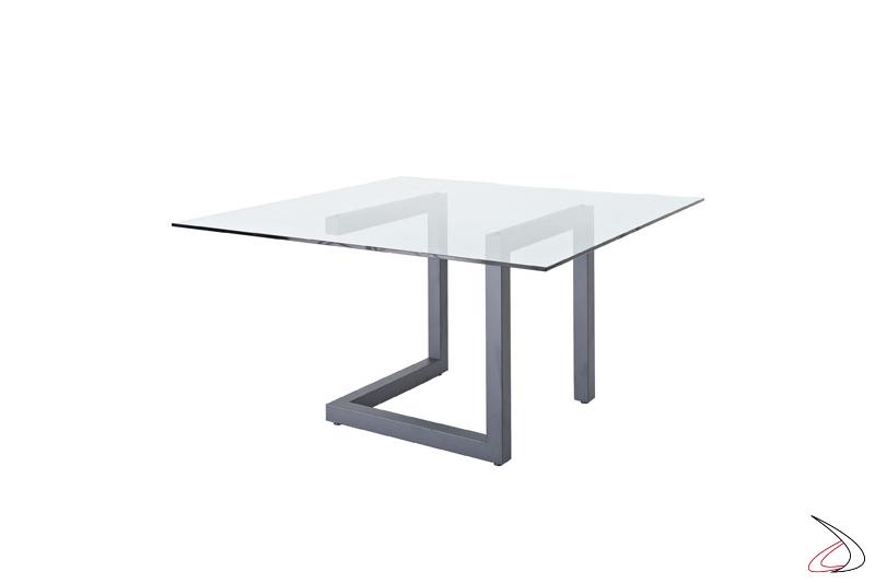 Tavolo quadrato con struttura in metallo color grigio piombo e piano in vetro temperato trasparente.