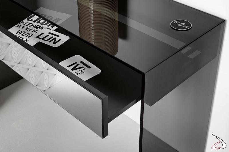 Consolle in vetro fumè, dal design moderno e sofisticato, con cassetto in legno e frontale a specchio. Optional caricabatteria wireless.