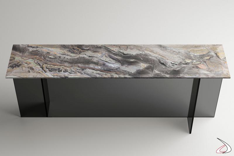 Consolle moderna e dal design essenziale, caratterizzato da una base in vetro formata da elementi verticali simmetrici e ortogonali che supporta un piano in marmo o vetro.