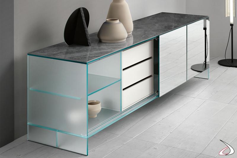 Credenza moderna e di design in vetro extrachiaro co top in ceramica, ante scorrevoli a specchio e cassetto laccato bianco opaco.