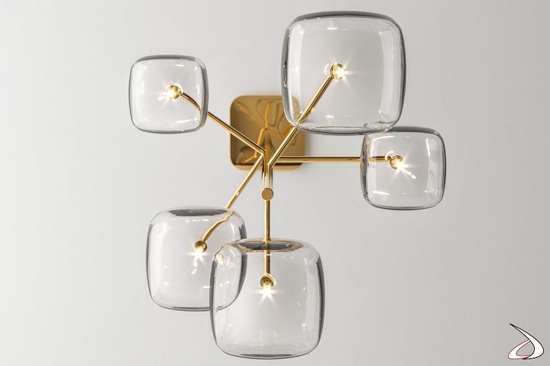 Lampada moderna e di design, caratterizzata da elementi in vetro dalla forma cubica arrotondata e struttura in metallo, in versione chandelier con 5 vetri.