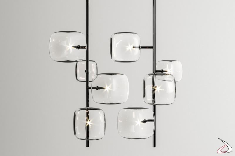 Lampada moderne e di design caratterizzata da elementi in vetro dalla forma cubica arrotondata e struttura in metallo. Modello a sospensione in versione verticale con 4 vetri.