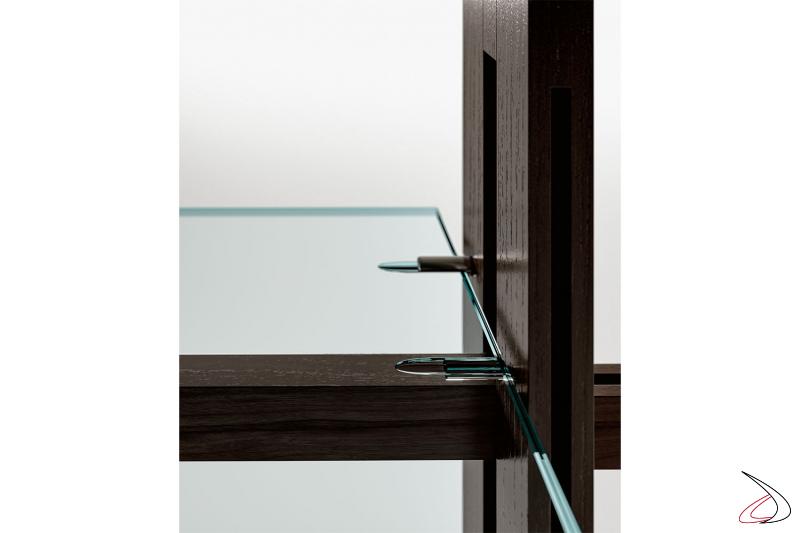 Libreria moderna con ripiani in vetro, con particolari asole laterali, che sono fissati ai montanti tramite incastro sui perni. Un sistema di sicurezza anticaduta è presente su ogni ripiano.