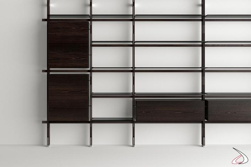 Libreria moderna ed elegante con struttura in legno massello, può accogliere contenitori orizzontali con apertura a ribalta verso il basso e contenitori verticali con anta a battente, realizzati con vetro e legno.