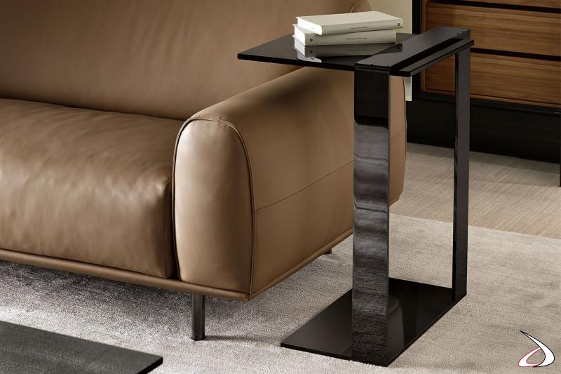 Tavolino fianco divano elegante e dal design minimalista, caratterizzato da una struttura in metallo che sostiene un top in vetro.