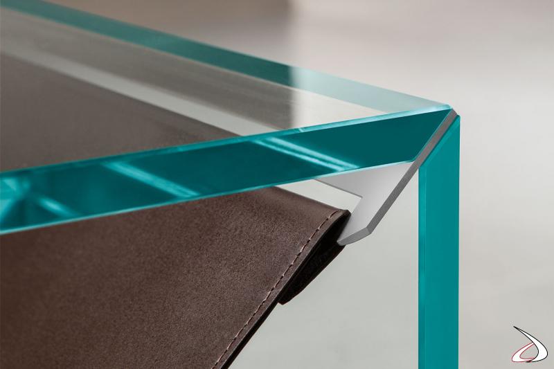 Dettaglio della giuntura impercettibile tra la struttura in vetro temperato e il ripiano in cuoio. Il supporto in metallo è disponibile in diverse finiture metalliche spazzolate.