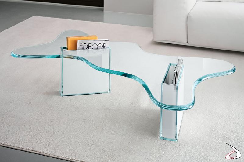 Tavolino moderno e di design in vetro, caratterizzato dala forma sagomata del top e il basamento che si trasforma in contenitori portariviste.