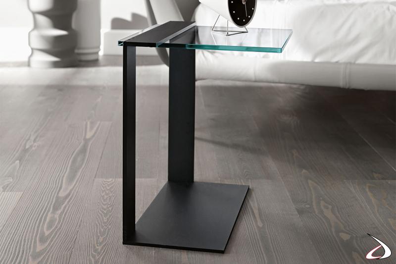 Tavolino rettangolare multiuso, caratterizzato da una struttura in metallo asimmetrica e un top in vetro.