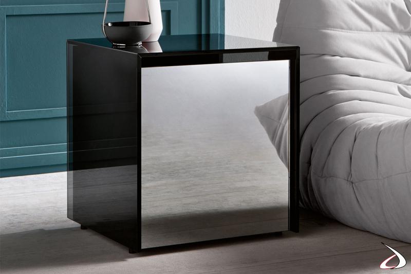 Tavolino fianco divano in vetro fumè, caratterizzato dal cassetto in legno con frontale a specchio che da luce all'ambiente.