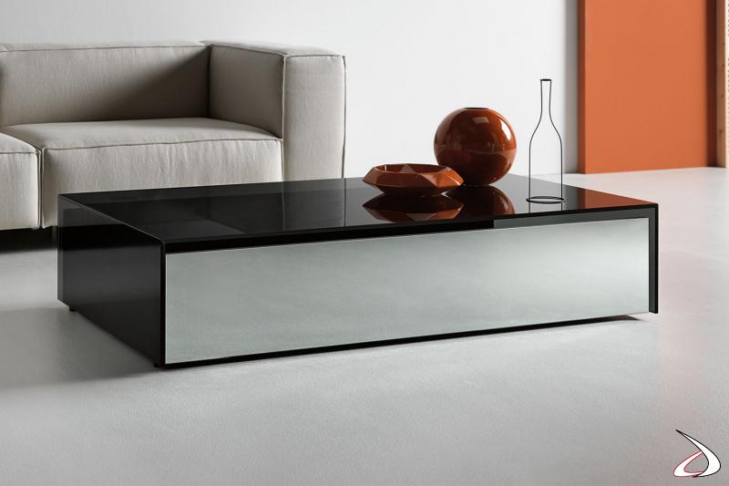 Tavolino basso rettangolare moderno e dal design funzionale. Il piano elegante in vetro racchiude dei cassetti in legno con frontale a specchio.