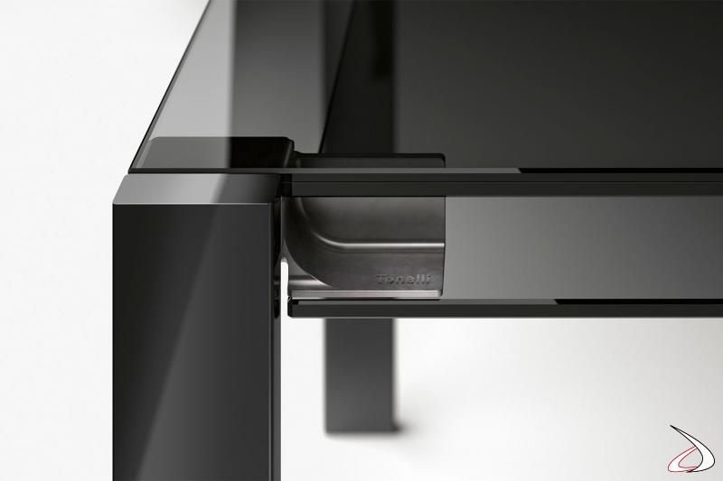 Tavolo moderno ed elegante allungabile dal design minimalista. Il movimento di apertura e chiusura del tavolo si compie con un semplice gesto, grazie al sistema di apertura degli allunghi in vetro realizzato con una speciale cerniera in fusione di acciaio
