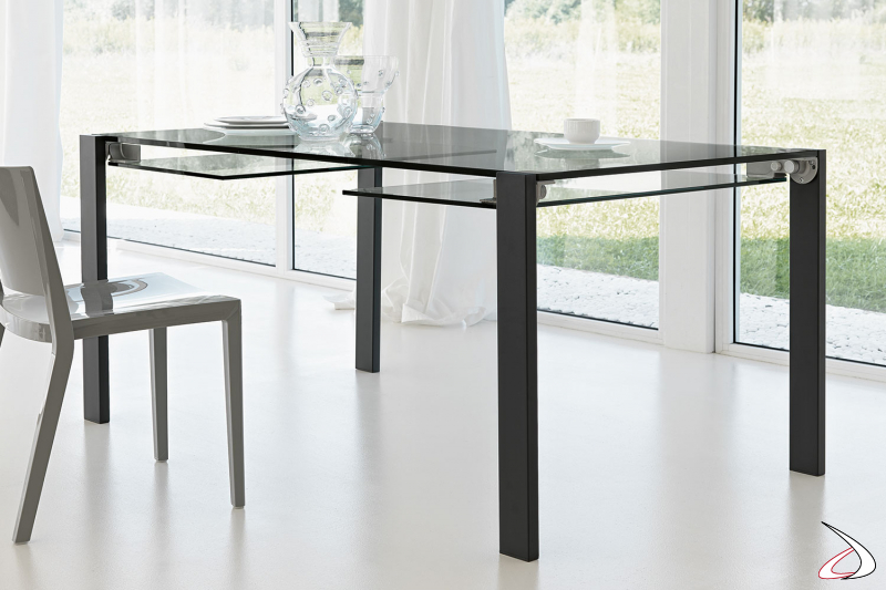 Tavolo moderno dal design minimalista e versatile, con top allungabile i vetro fumè e gambe in metallo verniciato nero.