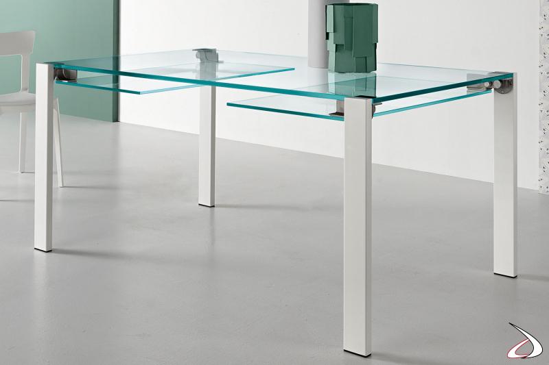 Tavolo elegante e dal design minimalista, con top allungabile in vetro e gambe in metallo verniciato bianco.