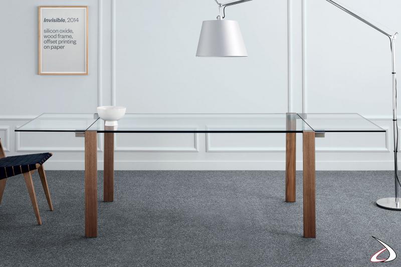 Elegante tavolo di design allungabile, con top rettangolare in vetro e gambe in noce canaletto.