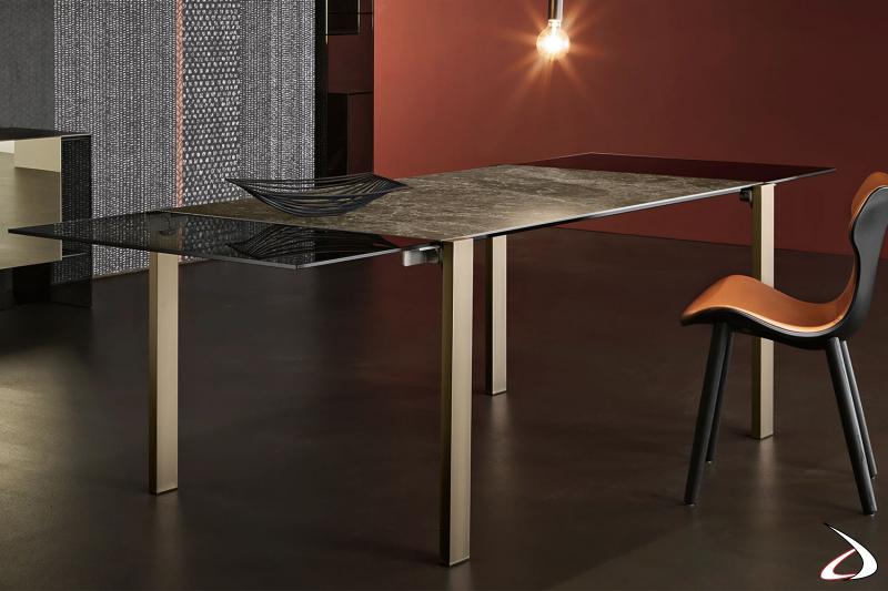 Tavolo elegante e di design con top rettangolre in ceramica Emperador e gabe i bronzo spazzolato, e allunghi in vetro fumè.