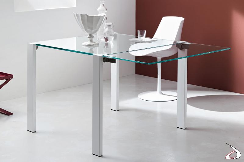 Tavolo moderno e minimalista, con gambe in metallo verniciato bianco e top in vetro con un allungo.