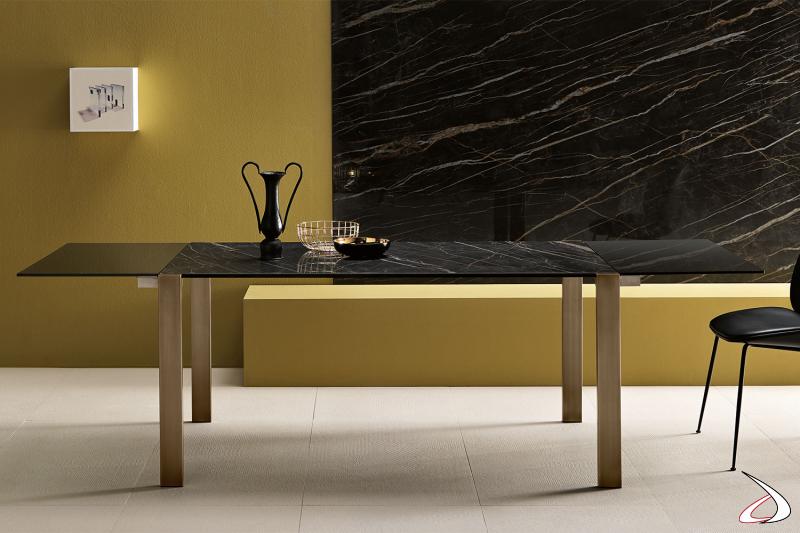 Tavolo moderno ed elegante con top in ceramica Noir Desir rettangolre e gambe in bronzo spazzolato. Allungabile con allunghi in vetro fumè.