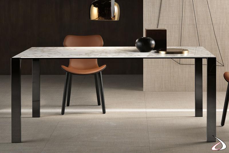 Tavolo moderno ed elegante rettangolare con top in ceramica calacatta arabescato e gambe in canna di fucile lucido.