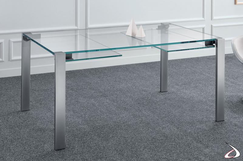 Tavolo moderno e minimalista, caratterizzato da un semplice top in vetro allungabile e gambe in metallo cromato opaco.