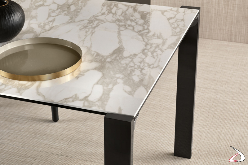Tavolo moderno ed elegante, caratterizzato da un design pulito e minimalista dove il top in ceramica è sostenuto da delle gambe perimetrali in metallo.