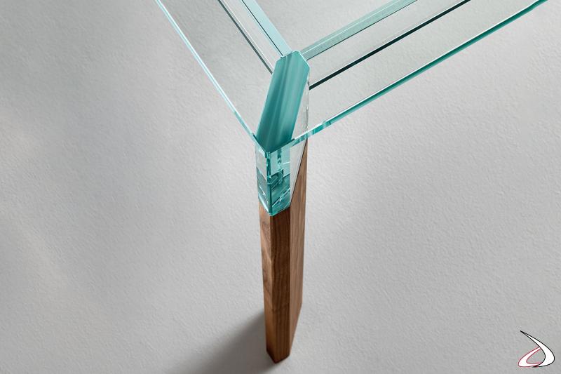 Tavolo moderno dal design minimalista che si caratterizza per il particolato top in vetro poggiato su gambe in noce canaletto sbontabili.