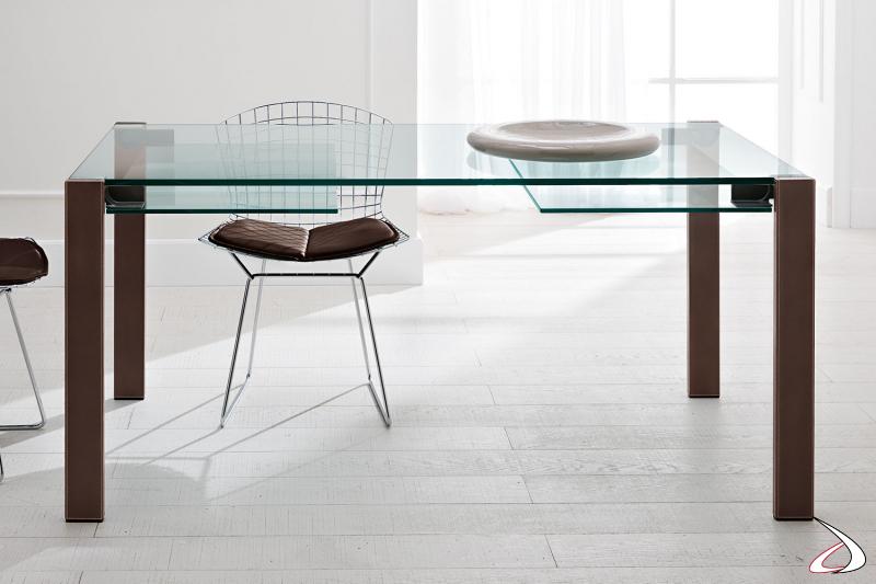 Tavolo elegante dal design minimalista con top in vetro e gambe in cuoio naturale.