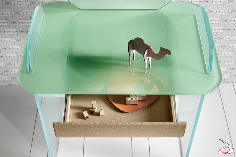 Dettaglio del piano in vetro opale verde della toeletta in vetro con cassetto rivestito in pelle beige.