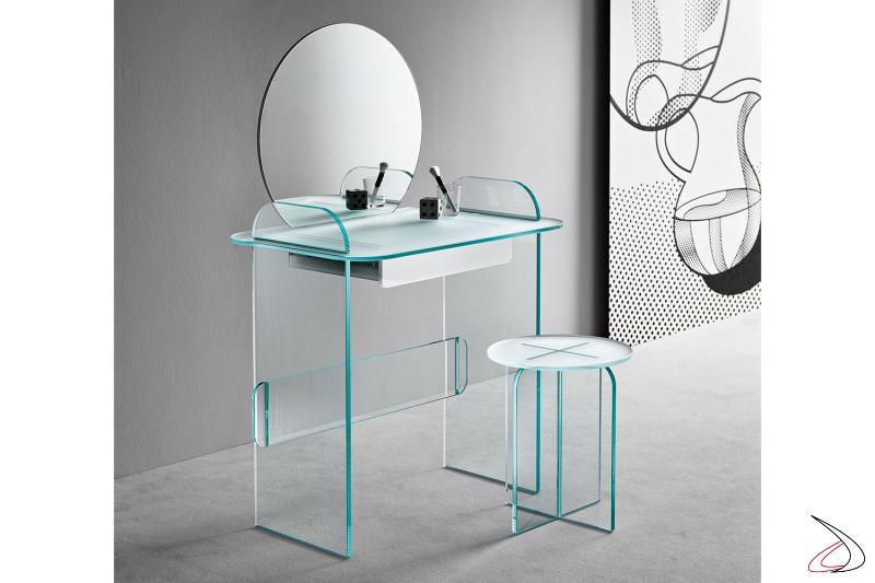 Toeletta in vetro, moderna e dal design ricercato. Si caratterizza per i fianchi che intersecano il top e dagli angoli smussati. Dispone di un cassetto in laccato bianco e specchio
