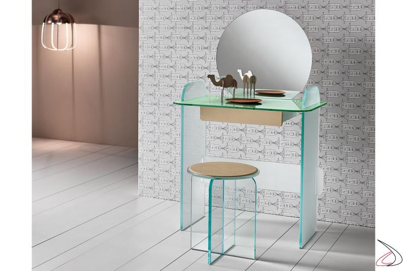 Teoeletta in vetro, moderna e dal design ricercato. Si caratterizza per gli elementi dagli angoli smussati che si intersecano. Cassetto con rivestimento in pelle beige.