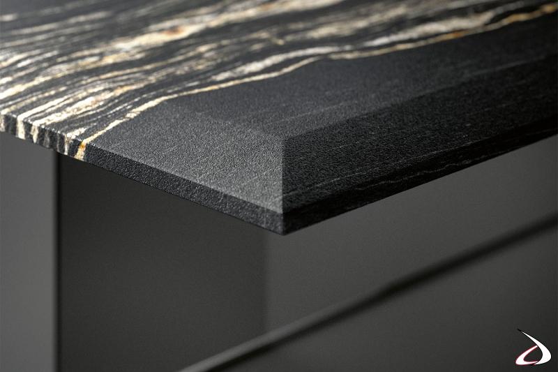 Dettaglio del piano in marmo spazzolato opaco, che viene arricchito dalla lavorazione di bisellatura a vista sul piano.