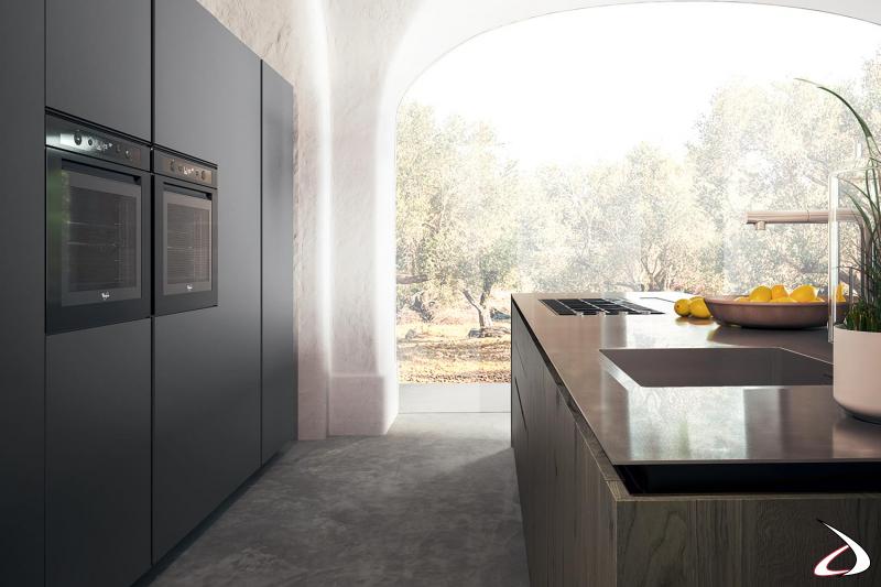 Cucina di design con colonna forno, colonna micronde e isola centrale con piano lavoro in acciaio