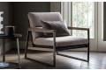Poltrona da salotto di design con struttura in metallo e seduta imbottita