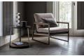Poltrona imbottita di design da salotto con schienale in pelle e seduta in tessuto