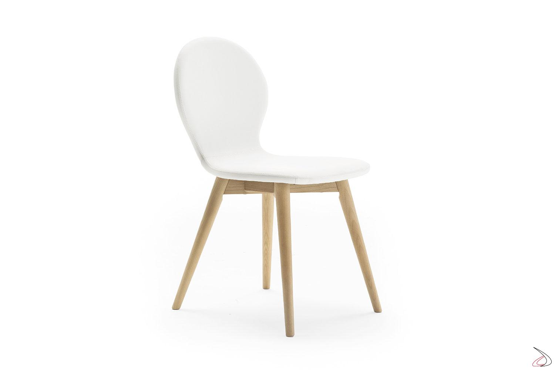 Sedia dal design semplice e sagomato, con seduta curvilinee imbottita e rivestita in ecopelle bianca, e caratterizzata da eleganti gambe cilindriche in legno.