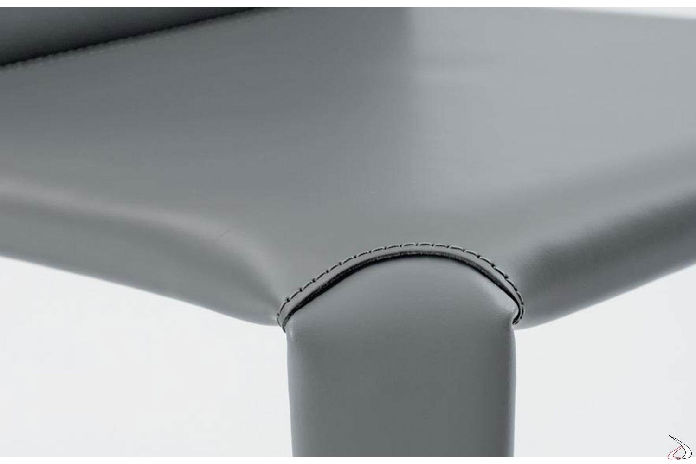 Dettaglio cucitura su cuoio in tinta con il colore grigio chiaro della seduta